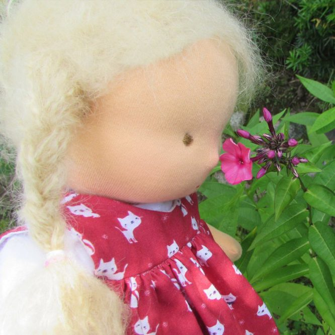 Waldorf doll smelling flowers