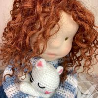 Waldorf inspired doll with curly natural brown hair and crocheted cat